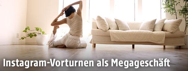 Frau macht Yoga-Übungen in ihrem Wohnzimmer
