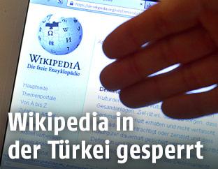 Hand deutet auf eine Wikipedia-Webseite