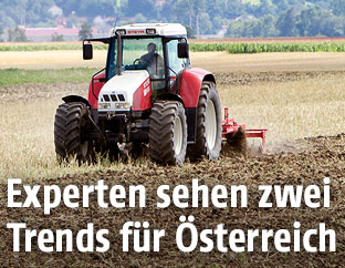 Traktor auf einem trockenen Feld bei der Ernte