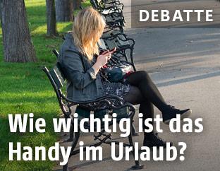 Frau mit Handy auf einer Parkbank