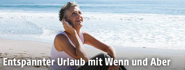 Eine Frau telefoniert am Strand