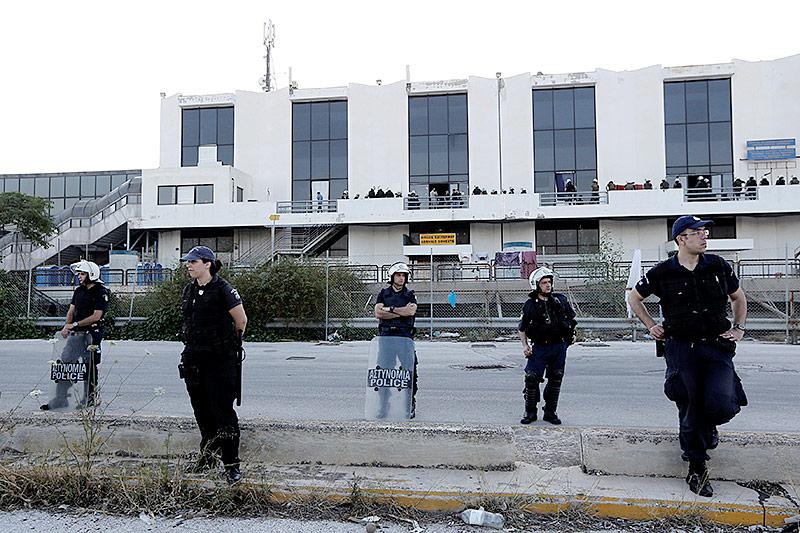 Griechische Polizisten umstellen ein Flüchtlingslager