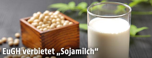 Ein Glas Sojamilch neben Sojabohnen