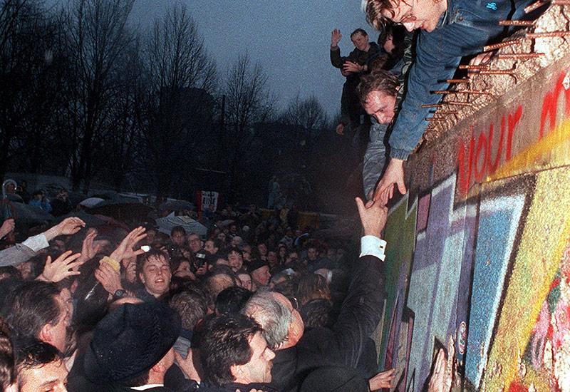 Helmut Kohl schüttelt die Hand eines Bürgers der über die Berliner Mauer geklettert ist