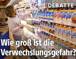 Eine Frau steht vor dem Milchregal im Supermarkt