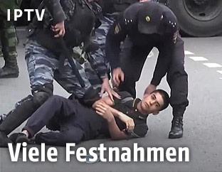 Ein Demonstrant in Moskau wird von Polizisten am Boden festgehalten