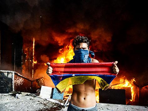 Demonstrant vor dem brennenden Gebäude