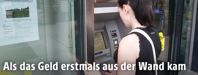 Kundin an einem Bankomaten