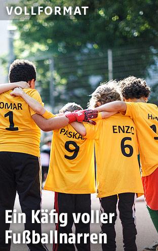 Kinder im Fußballdress stehen Arm in Arm in einem Fußballkäfig