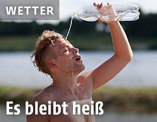 Ein Mann kühlt sich mit Wasser aus der Flasche ab