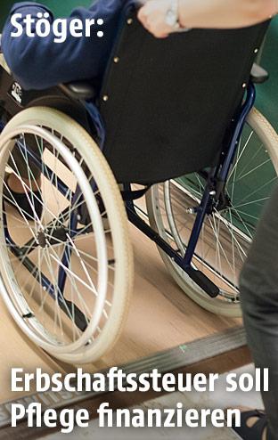 Eine Pflegerin schiebt eine Frau im Rollstuhl
