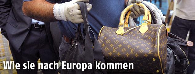 Zollbeamter hält gefälschte Taschen