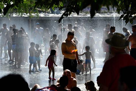 Menschen suchen Abkühlen bei einem Brunnen in Madrid