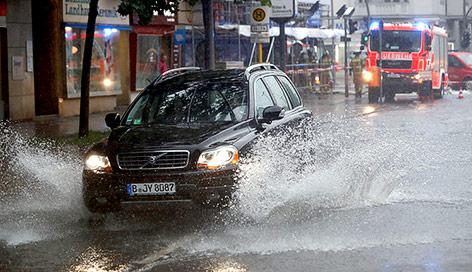Auto fährt auf einer überfluteten Straße