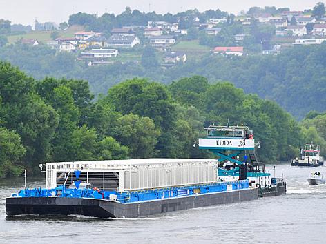 """Das Schubboot """"Edda"""" schiebt in Obrigheim (Baden-Württemberg) auf dem Neckar vor dem Atomkraftwerk ein mit drei Castoren beladenes Transportschiff."""