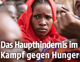 Frau aus dem Südsudan wartet mit anderen Menschen in einem Auffanglager auf humanitäre Hilfe