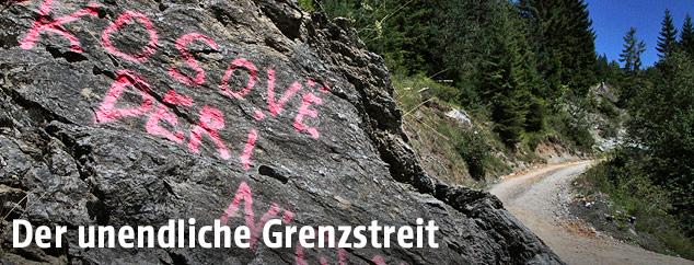 Mit Parolen beschmierter Stein bei der Grenze Kosovos zu Montenegro