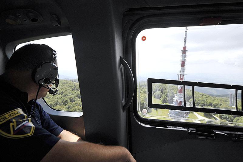 Polizist in einem Helikopter blickt auf den Fernsehmast auf dem Berg Sveta Gera