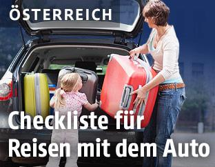 Frau und Tochter räumen einen Kofferraum ein