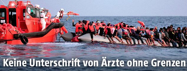 Helfer werfen von einem Boot Menschen in einem Flüchtlingsboot Schwimmwesten zu