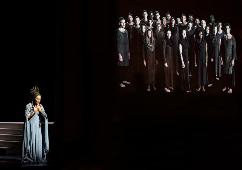 Aida vor Video-Wand mit Darstellern in Schwarzweiss