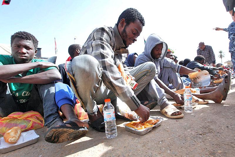 Migranten essen in einem libyschen Lager auf dem Boden