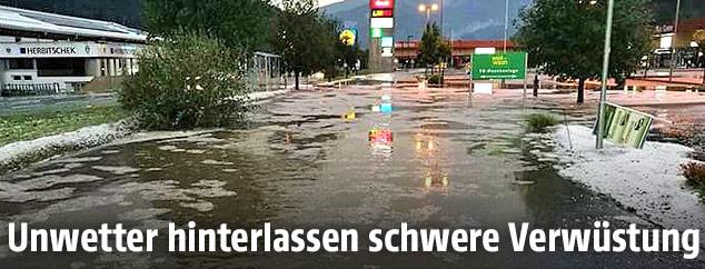 Überschwemmte und mit Hagel bedeckte Straße