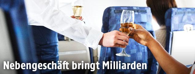 Flugbegleiterin bringt einem Gast ein Glas Sekt