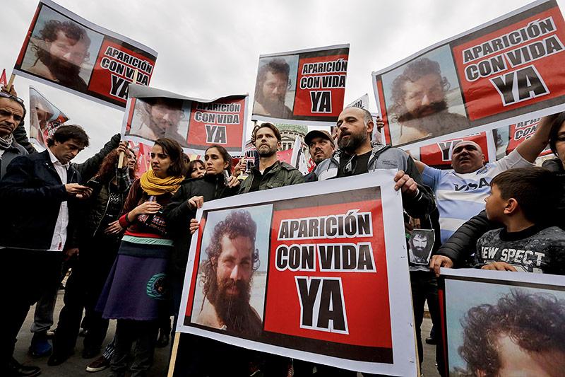 """Verwandte von Aktivisten mit Santiago Maldonado halten Schilder mit dem Aufruf """"Erscheine jetzt lebend"""""""