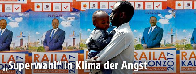 Ein Mann geht mit Kind an Wahlplakaten in Kenias Hauptstadt Nairobi vorbei