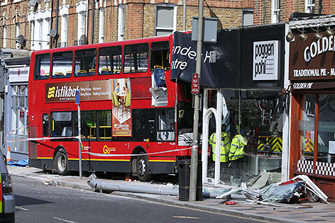 Doppeldeckerbus und zerstörtes Eckgeschäft