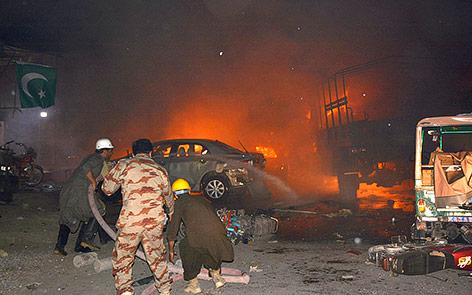 Feuerwehrleute löschen ein brennendes Auto
