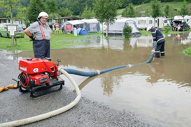 Feuerwehrmänner pumpen Wasser vom überfluteten Campingplatz ab