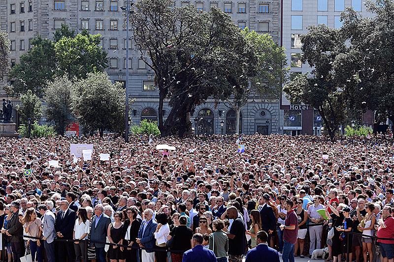Menschen halten am Plaza de Catalunya in Barcelona eine Trauerminute ab