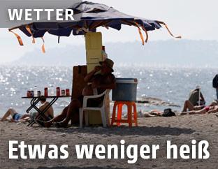 Mann sitzt am Strand unter einem Sonnenschirm
