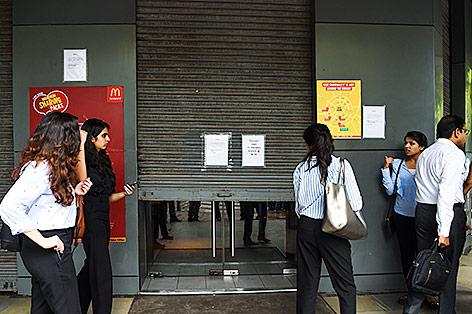 Inder stehen vor einer geschlossenen McDonalds-Filiale in Neu Delhi