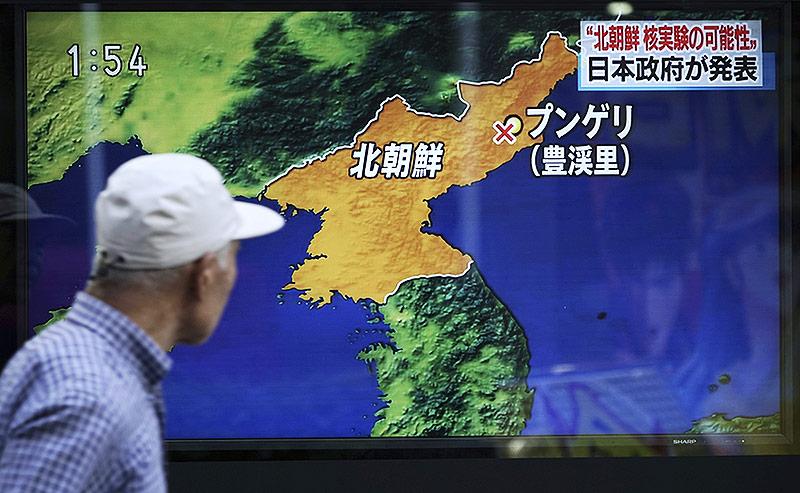 Fußgänger in Tokio passiert einen Fernseher in einer Auslage, mit dem Bericht über den Atomtest