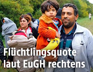 Ein Migrant trägt ein Kind