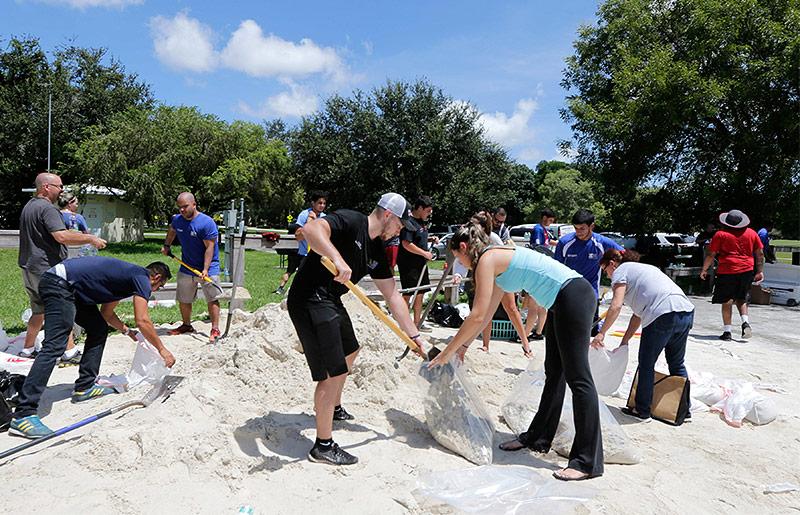 Menschen befüllen Sandsäcke