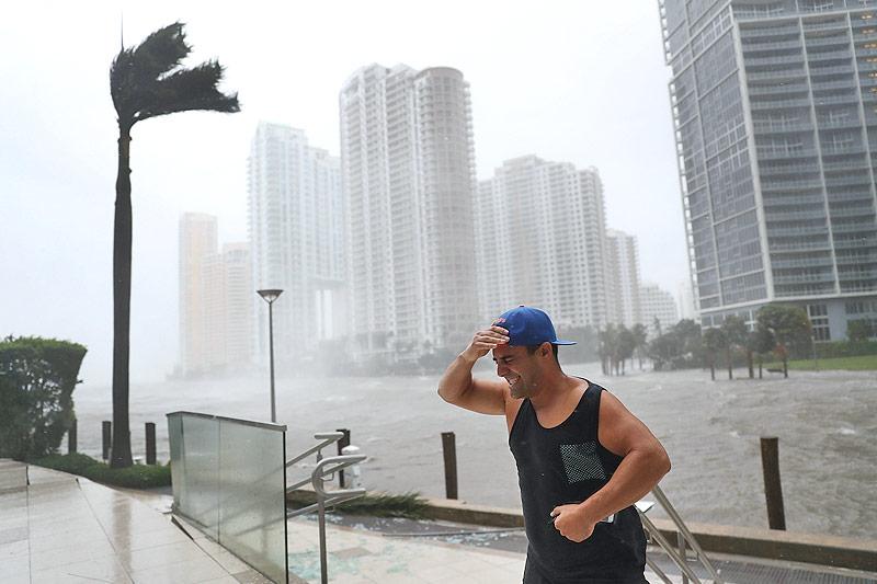 Ein Mann kämpft am über die Ufer getretenen Miami River in Miami gegen den Wind an