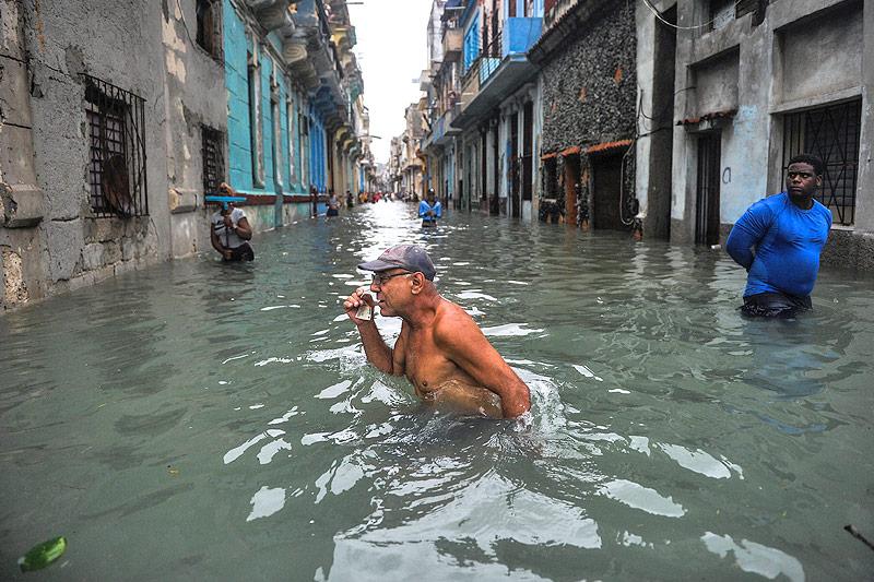 Personen auf überfluteter Straße in der kubanischen Hauptstadt Havanna