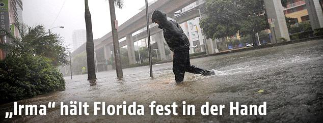 Ein Mann überquert im Regen eine überschwemmte Straße in Miami