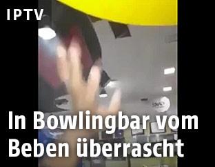 Ein Mann in einer Bowlingbar hält die Hand in die Höhe