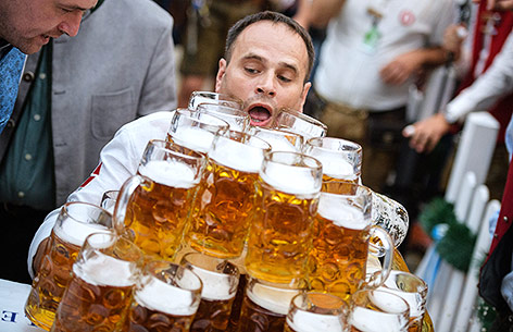 Oliver Strümpfel trägt mehrere gefüllte Maßkrüge
