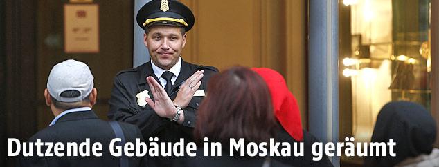 Ein Moskauer Polizist verwehrt Menschen den Zugang zu einem Gebäude