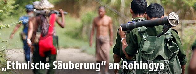 Bewaffente Soldaten und Polizisten patroullieren auf einer Straße in Myanmar
