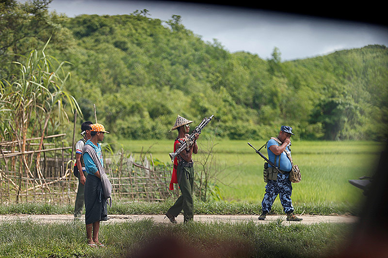 Ein bewaffneter Soldat und ein bewaffneter Polizist patroulliern auf einer Straße in Myanmar