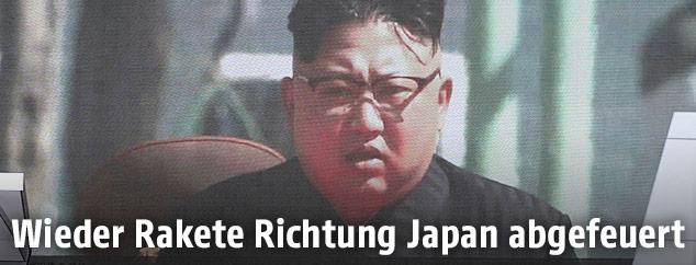 Nordkoreas Machthaber Kim Jong-Un auf einem Bildschirm während der Nachrichten über den Raketentest