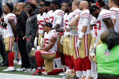 NFL-Spieler Eric Reid kniet während der Nationalhymne