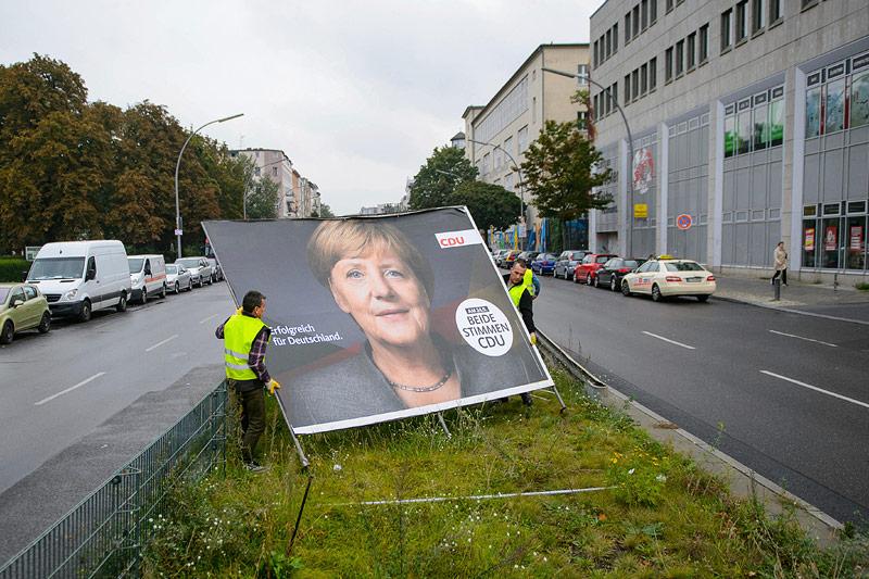 Arbeiter entfernen Plakat mit Angela Merkel